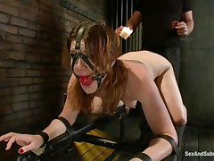 Cici Rhodes likes the dungeon. Belted to a board, fastened and gagged the brunette acquires a punishment with hot wax and spanking. Her corporalist removes a metal plug from her ass, then re-inserts it, attaching a rope from it to her head. A dildo runs over her pussy, making her want to cum, but can't yet.
