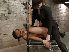 With her feet bound up and metal clamps all over her body the ebon slut endures a harsh punishment. This dominatrix-bitch knows what he's doing and gives her both pain and pleasure. She can't even shriek as her throat is folded with scotch tape. Look at that hairless cunt and how deep she's rubbing it with the vibrator.